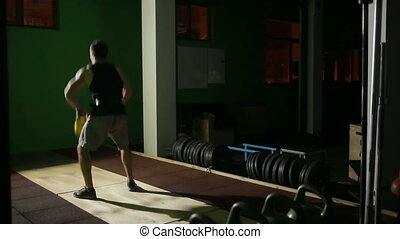 Young athletic man doing kettlebell swing exercise at the gym. CrossFit