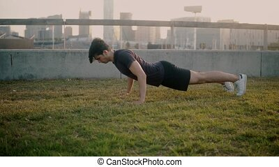 Young athletic man doing pushups exercises at park with...