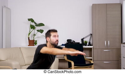 Young athletic man doing squats in the living room. Close up
