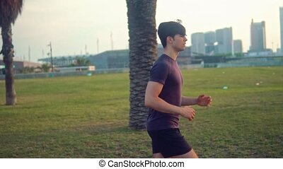 Young athletic man running at palm tree park near the beach....