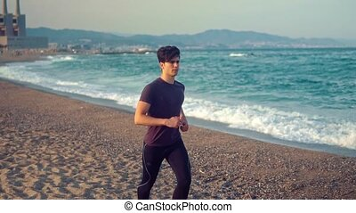 Young athletic man running at the beach. Health concept -...