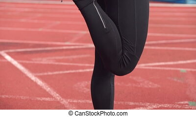 Young athletic man stretching legs before run on running track.