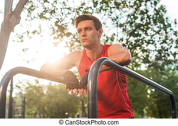 Young athletic man taking a break during working out outdoor.