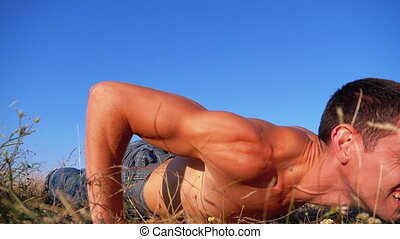 Young Athletic Man with a Bare Torso Performs Push-ups with...