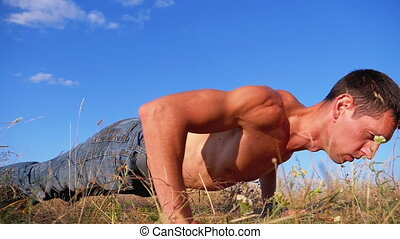 Young Athletic Man with a Bare Torso Performs Pushups on the...