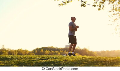 young athletic runner doing stretching exercise, preparing for workout in the park. sunset, toned video
