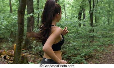 Young athletic sporty girl with long hair training in green forest during summer spring season with lots of leaves fallen on forest path.