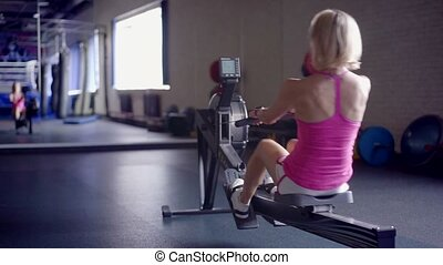Young athletic woman doing rowing machine workout at the gym