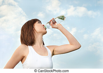 Young athletic woman drinking mineral water
