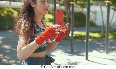 Young athletic woman engaged in boxing outdoors in summer park