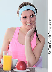 young athletic woman having breakfast at home