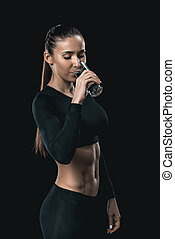 Young athletic woman in sportswear drinking water, healthy living concept