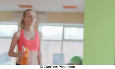 Young athletic woman is drinking water after training on the sport mat.