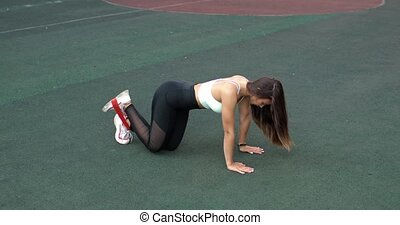Young athletic woman is training doing exercise for legs using resistance band.
