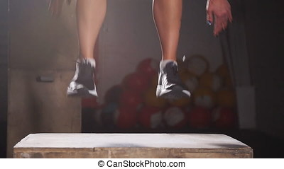 Young athletic woman jumping up on the box. Slow motion.