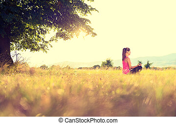 Young athletic woman practicing yoga on a meadow at sunset, image with lens flare
