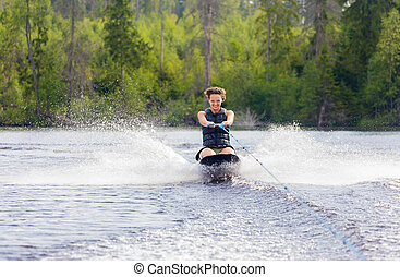 Young athletic woman riding kneeboard on a lake