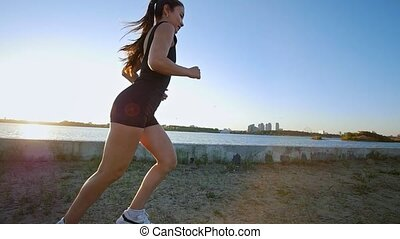 Young Athletic Woman Running Near The River In Slow Motion