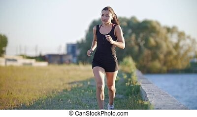Young Athletic Woman Running Near The River