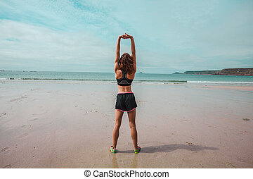 Young athletic woman stretching on the beach