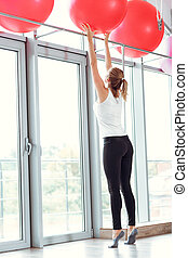 Young athletic woman taking red fitness ball in gym