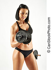 Young athletic woman working out with dumbbells