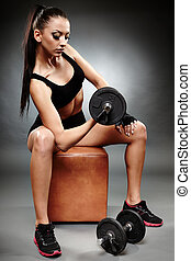Young athletic woman working with heavy dumbbells