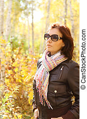 Young atractive woman in the sunny autumn forest