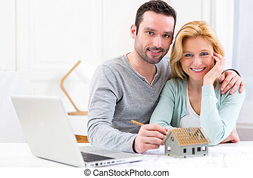 Young attractive 30s couple making home project - View of a...