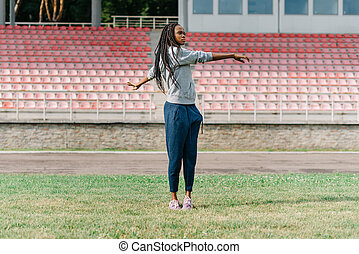 Young attractive African American female working out outdoors at a stadium