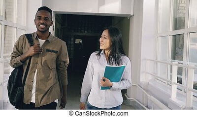 Young attractive african male and asian female students are...