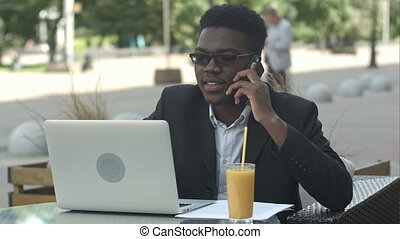 Young attractive afro american businessman with glasses and laptop sitting in cafe bar and talking on cell phone
