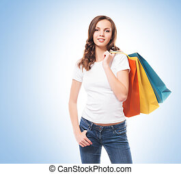 Young, attractive and happy shopping girl with bright shopping b