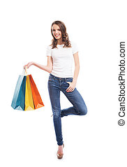 Young, attractive and happy shopping girl with the bright shopping bags isolated on white