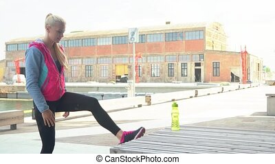 Young, attractive and sporty blond girl doing warm up...