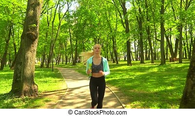 Young, attractive and sporty blond girl jogging outdoor in...