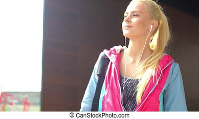 Young, attractive and sporty blond girl walking outdoor with...