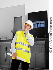 young attractive architect worker supervising building blueprints outdoors wearing construction helmet