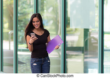 Young attractive Asian student typing a message on her smart-phone while walking outdoors
