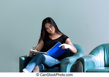 Young attractive asian woman studying her notebook in preparation for a school exam