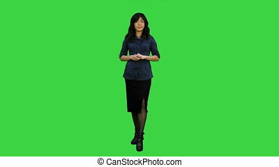 Young attractive asian woman talks to camera, presenting something on a Green Screen, Chroma Key