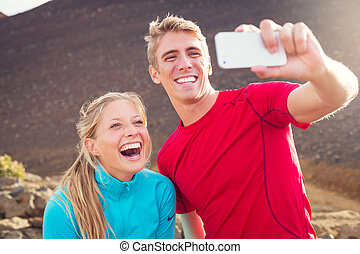 Young attractive athletic couple taking photo of themselves...