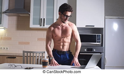 Young attractive athletic man in the kitchen looking at laptop.