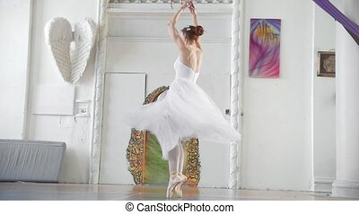 Young attractive ballerina in white tutu performs pirouette...