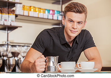 young attractive barista adding milk. handsome man made...