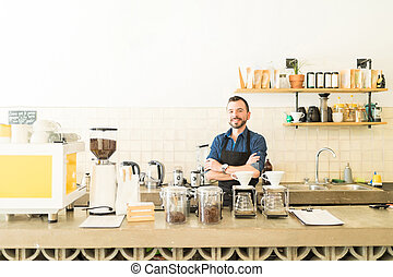 Young attractive barista in a cafe - Wide view of a good...