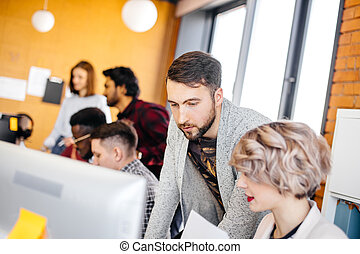 young attractive bearded guy is looking at the screen of secretary's computer