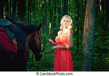 Young attractive blond girl with a horse in the forest