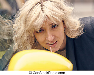 Young attractive blond woman paints her lips