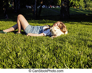 young attractive blond woman playing with her dog in green park at summer, lifestyle people concept